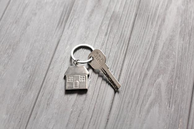 Schlüssel mit kleinem haus auf holztisch