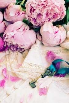 Schlüssel mit rosa pfingstrosenblumen auf vintage-spitzenkleidungsstück