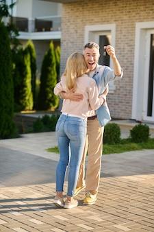 Schlüssel, neues zuhause. begeisterter junger erwachsener mann mit offenem mund, der am schönen nachmittag schlüssel zeigt, die eine langhaarige frau in der nähe des neuen hauses umarmen