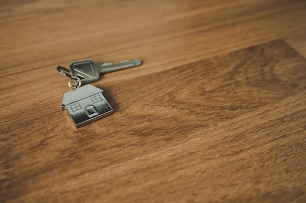 Schlüssel und ein schlüsselanhängerförmiges haus auf holzboden im zimmer. immobilieninvestition und haushypothek-finanzimmobilienkonzept