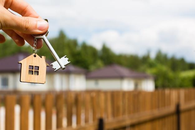 Schlüssel und hölzerner schlüsselbund in form eines hauses in der hand