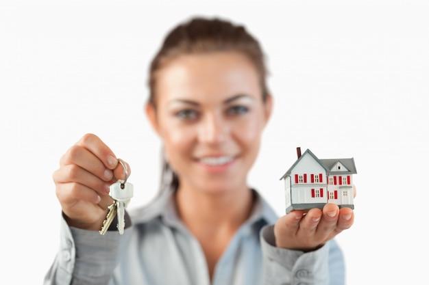 Schlüssel und miniaturhaus, das von der weiblichen immobilienmaklerin präsentiert wird