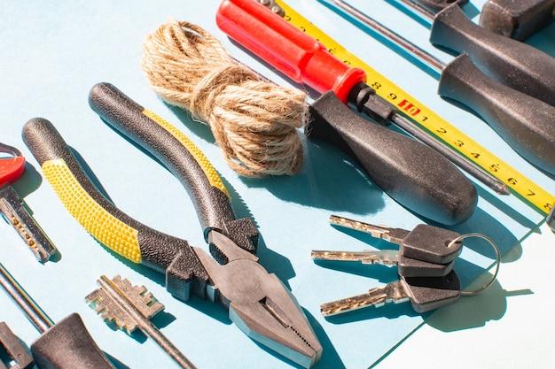 Schlüssel und verschiedene werkzeuge auf hellblauem hintergrund im sonnenlicht