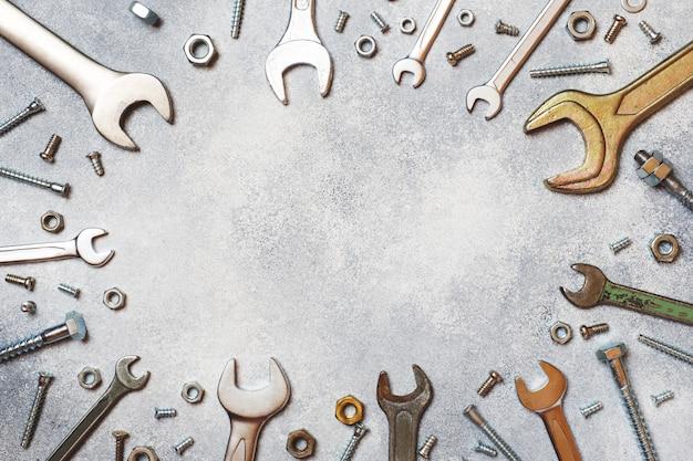 Schlüssel, werkzeugbolzen und nüsse auf grauem konkretem hintergrund mit kopienraum.