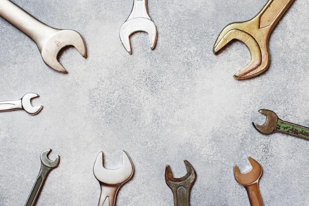 Schlüssel, werkzeuge auf grauem konkretem hintergrund mit kopienraum.