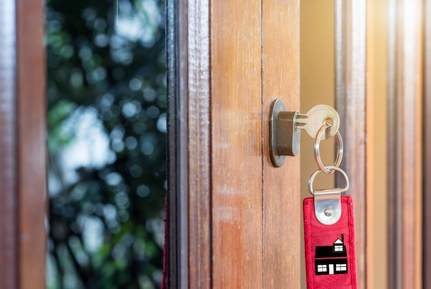 Schlüssel zur hand von menschen öffnen die tür nach innen, außentür offen in die haustür setzen