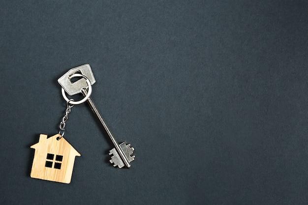 Schlüsselanhänger in der form des holzhauses mit schlüssel auf einem schwarzen hintergrund