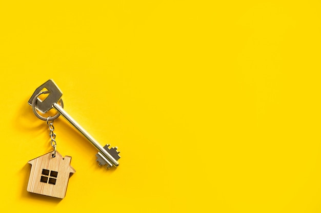 Schlüsselanhänger in der form des holzhauses mit schlüssel auf gelbem hintergrund.