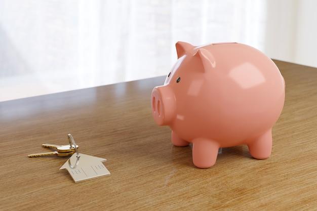 Schlüsselanhänger in form eines hauses neben einem sparschwein auf einem tisch. konzept für den immobilienkauf.