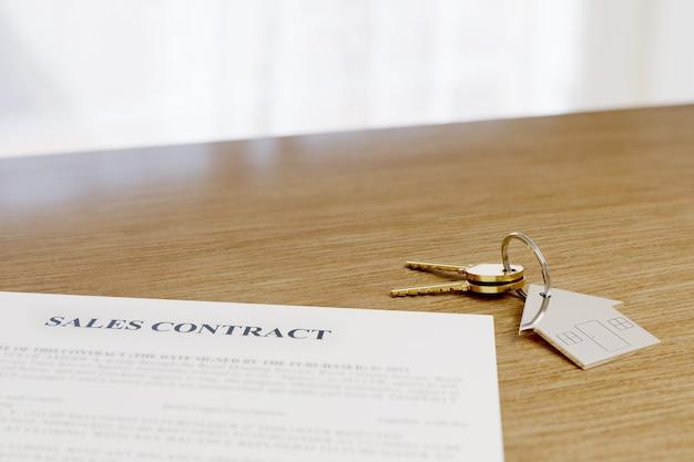 Schlüsselanhänger in form eines hauses neben einem vertrag. konzept für den immobilienkauf.