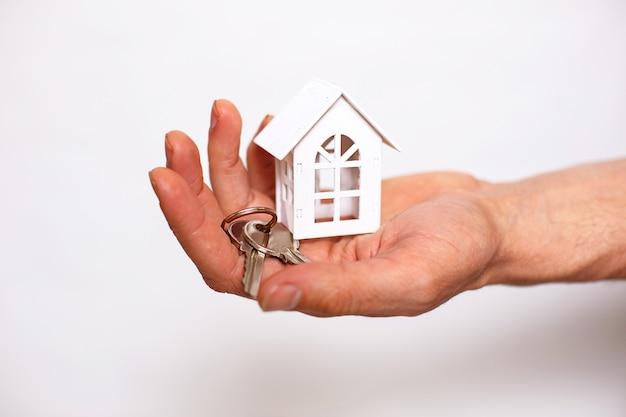 Schlüsselanhänger mit hausschlüsseln an der hand eines mannes auf weißem hintergrund. immobilienmakler, verkauf neuer eigenheime, hypotheken, umzug, bankgeschäfte, reparatur und bau
