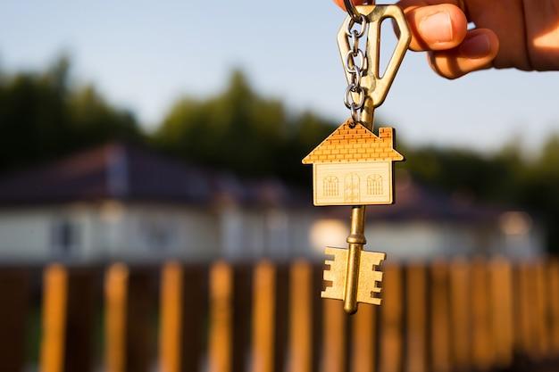 Schlüsselanhänger mit schlüsselbundhaus in der hand. umzug in ein neues zuhause, hypothek, vermietung und buchung von wohnungen
