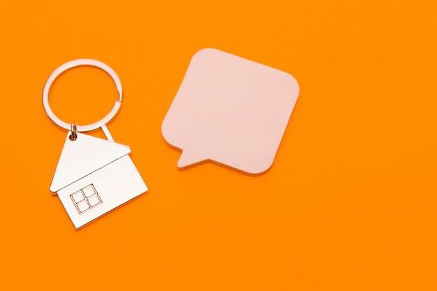 Schlüsselbund in form eines hauses und aufkleber auf einem orangefarbenen hintergrund