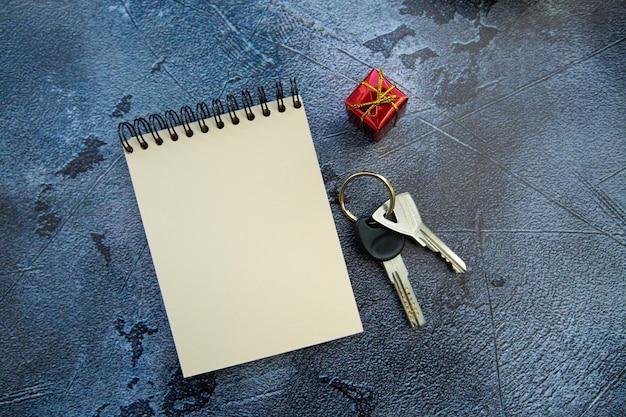 Schlüsselbund, notizblock und ein kleines geschenk auf einem grauen hintergrund. wohnung als geschenk