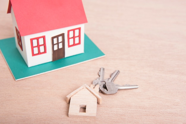 Schlüsselnach- und -modellhaus auf hölzernem tabellenhintergrund.