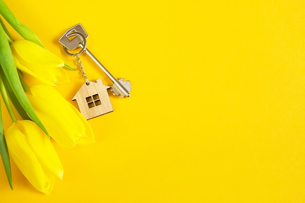 Schlüsselring in form eines holzhauses mit schlüssel auf gelbem hintergrund und frühlingstulpen.