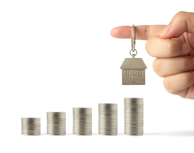 Schlüsselring-miniaturhaus in der hand auf wachsendem stapel von geldgeld, das auf weiß isoliert wird