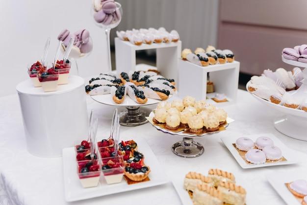 Schmackhafte auswahl an leckeren desserts, kuchen, cupcakes und gebäck auf einem buffettisch bei bankett, party oder hochzeit