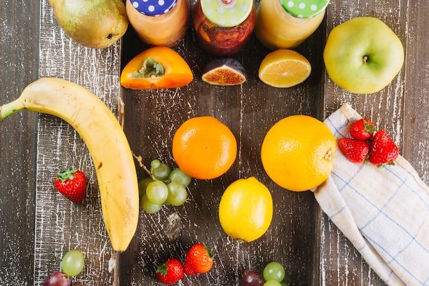 Schmackhafte früchte in der nähe von flaschen