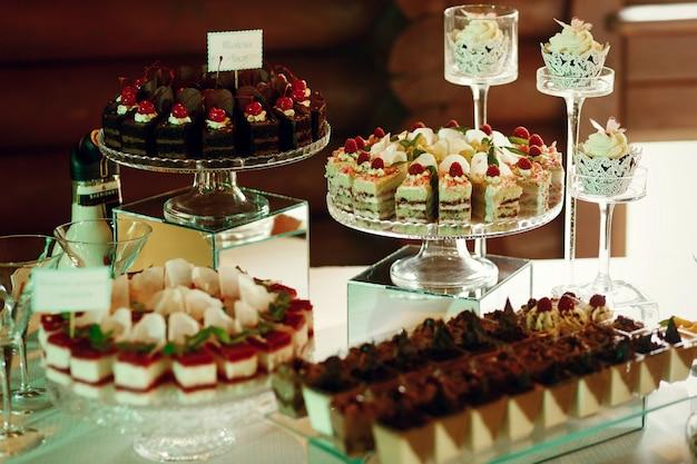 Schmackhafte früchte und schokoladenkuchen stehen auf glasplatten
