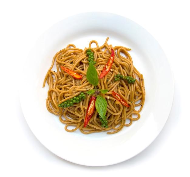 Schmackhafte scharfe und würzige soße der spaghettis mit der draufsicht der traditionellen thailändischen u. italienischen küchefusionsart des frischen basilikums, des jungen grünen und roten pfeffers lokalisiert