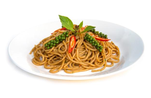 Schmackhafte scharfe und würzige soße der spaghettis mit der seitenansicht der traditionellen thailändischen u. italienischen küchefusions-art des frischen basilikums, des jungen grünen und roten pfeffers lokalisiert