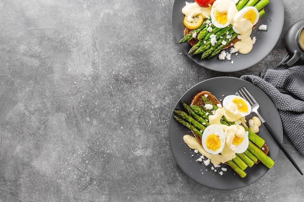 Schmackhafte toasts mit spargel, eiern und soße