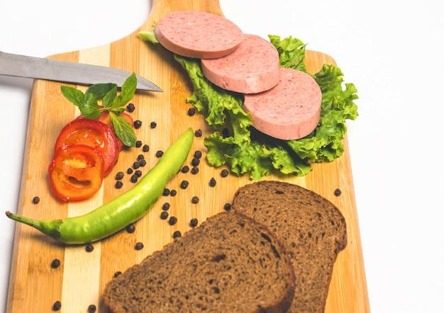 Schmackhafte wurst und brot mit salat und tomaten zum mittagessen