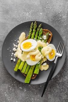 Schmackhafter toast mit spargel, eiern und soße