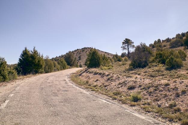 Schmale asphaltgebirgsstraße ohne das autofahren an einem sonnigen tag