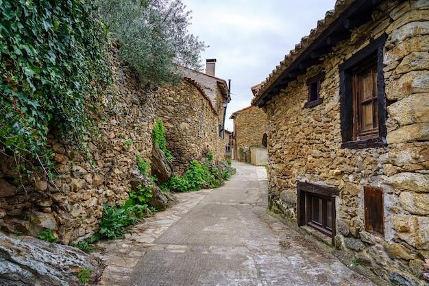 Schmale gasse in einer alten mittelalterlichen stadt aus stein in der sierra de madrid. horcajuelo. spanien.