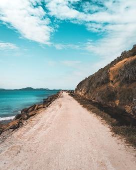 Schmale sandstraße entlang des meeres und hohe steile hügel mit einem schönen bewölkten blauen himmel