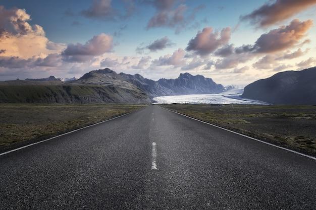 Schmale straße, die zu hohen felsigen bergen im skaftafell-nationalpark in island führt