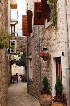 Schmale straße mit geöffneten fensterläden an fenstern in der altstadt von budva montenegro