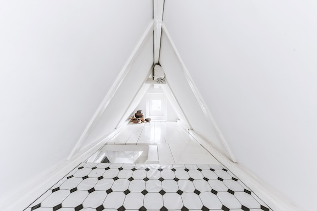 Schmaler dachraum mit wänden aus konischem dach, dekoriert mit ziegeln und weißer farbe