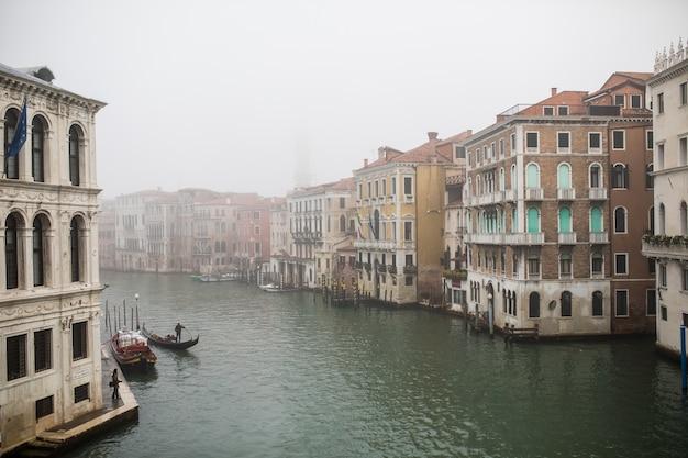 Schmaler kanal unter alten bunten backsteinhäusern in venedig, italien.