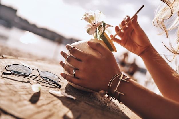 Schmeckt nach sommer! nahaufnahme einer jungen frau, die kokoscocktail mit ihren händen hält, während sie sich am strand ausruht?