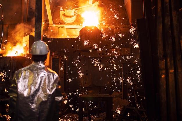 Schmelzeisen in der gießerei und arbeiter, die den prozess eisenguss und -produktion, metallurgie und schwerindustrie kontrollieren.