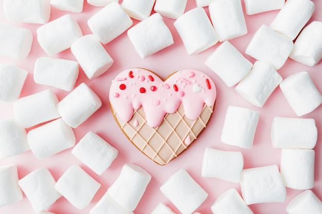 Schmelzen sie eis herz herz lebkuchen keks, marshmallow. valentinstag. rosa hintergrund. hochwertiges foto