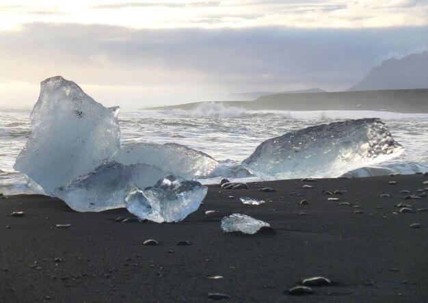 Schmelzende große eisberge auf dem schwarzen sandstrand von südisland