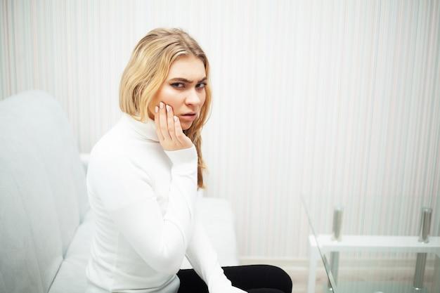Schmerzen. das problem der zähne. eine frau hat zahnschmerzen. ein bild von einem schönen, traurigen mädchen, das unter starken schmerzen in den zähnen leidet. eine attraktive frau empfindet schmerzhafte zahnschmerzen