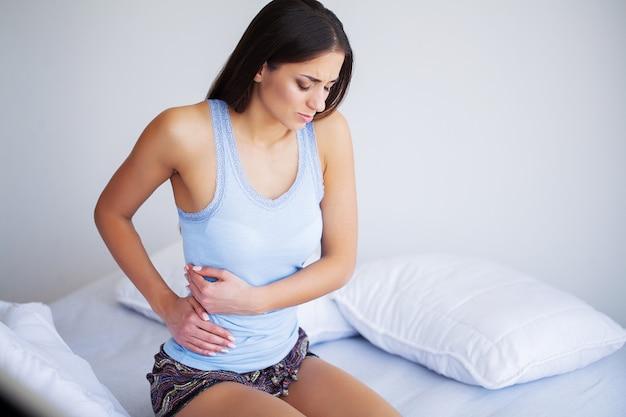 Schmerzen im bauch. frau, die schmerzliche magenschmerzen hat, frau, die unter bauchschmerzen leidet