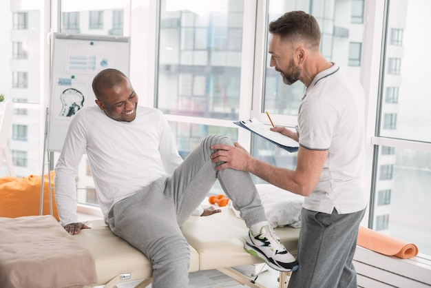 Schmerzen im bein. unglücklicher freudloser mann, der unter schmerzen leidet, während er seinen hals beugt