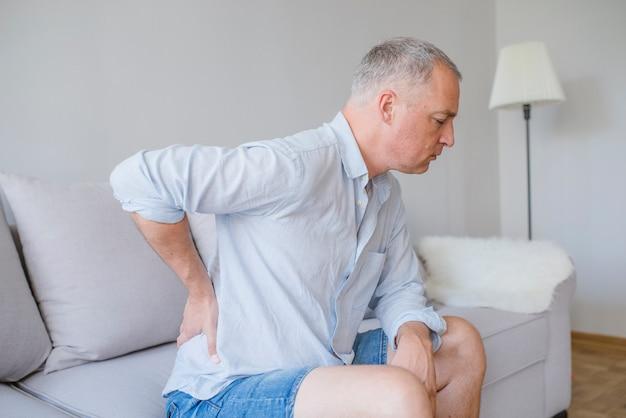 Schmerzen im unteren rückenbereich. mann, der zurück in den schmerz hält. medizinisches konzept.