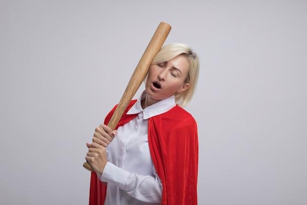 Schmerzende blonde superheldin mittleren alters im roten umhang, die sich mit einem baseballschläger mit geschlossenen augen auf den kopf schlägt