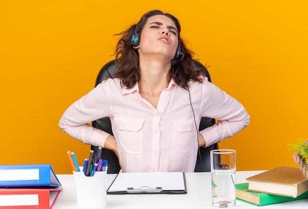 Schmerzende hübsche kaukasische call-center-betreiberin auf kopfhörern, die am schreibtisch sitzen, mit bürowerkzeugen, die sie isoliert auf oranger wand halten?