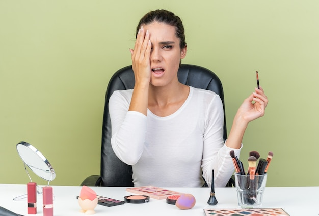 Schmerzende hübsche kaukasische frau, die am tisch mit make-up-tools sitzt, die hand auf ihr auge legt und make-up-pinsel isoliert auf olivgrüner wand mit kopierraum hält