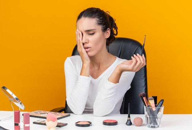 Schmerzende hübsche kaukasische frau, die am tisch mit make-up-tools sitzt, die hand auf ihr auge legt und make-up-pinsel isoliert auf oranger wand mit kopierraum hält