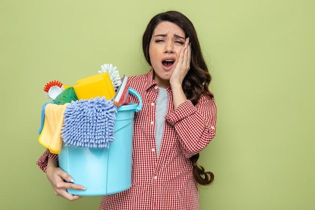 Schmerzende hübsche kaukasische putzfrau, die reinigungsgeräte hält und die hand auf ihr gesicht legt