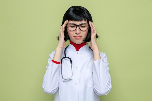 Schmerzende junge hübsche kaukasische frau mit brille, die eine arztuniform mit stethoskop trägt und die hände auf ihre schläfe legt, die mit geschlossenen augen steht